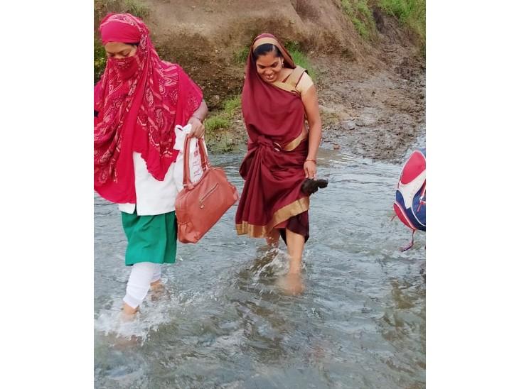 नदी पार करते हुए स्वास्थ कार्यकर्ता - Dainik Bhaskar