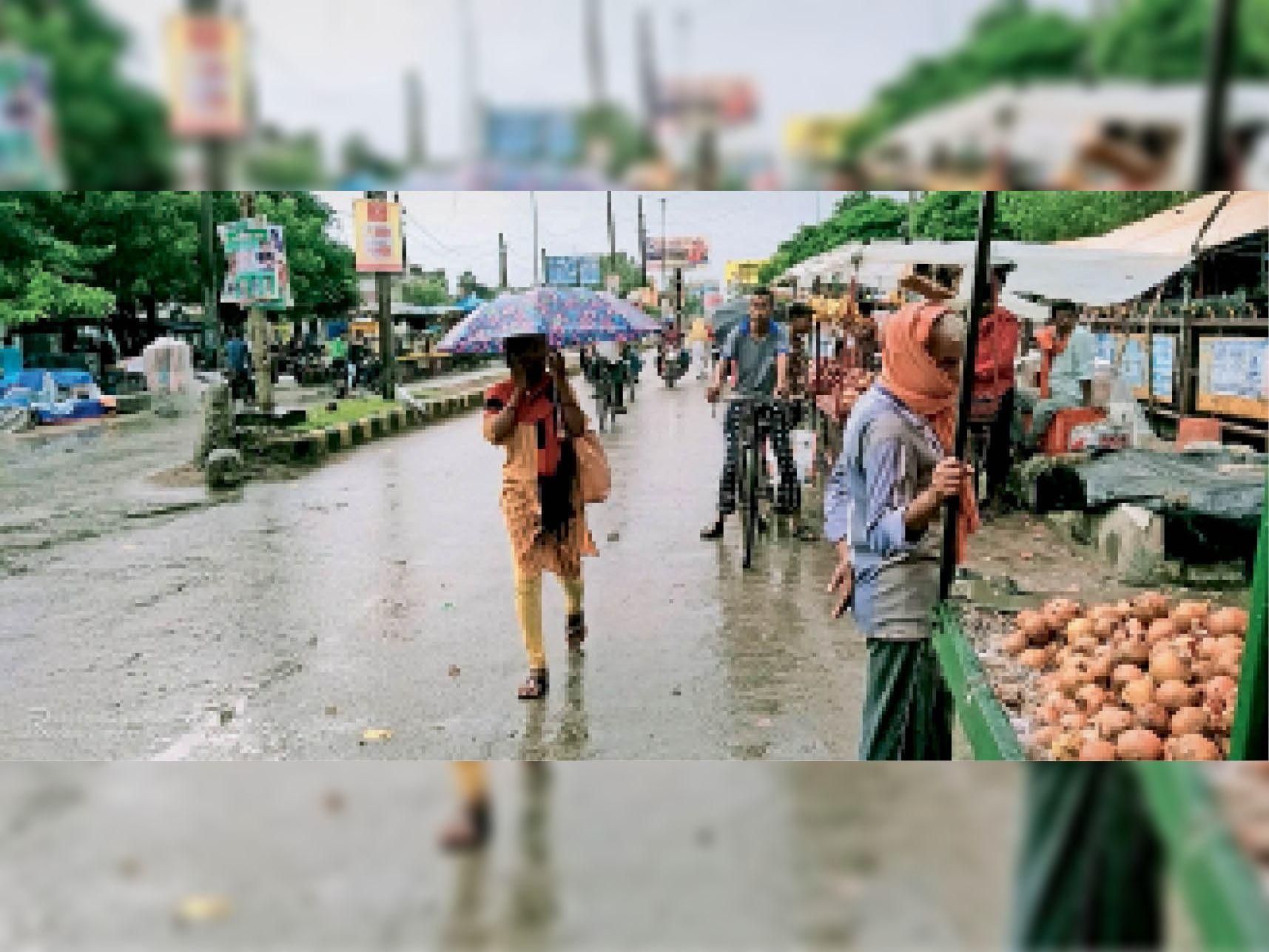बारिश से बचने के लिए छाता लगाकर जाती युवती। - Dainik Bhaskar