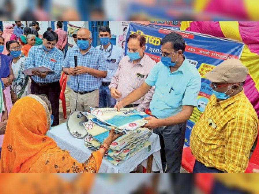 मेडिकेटेड मच्छरदानी वितरण करते अधिकारी। - Dainik Bhaskar