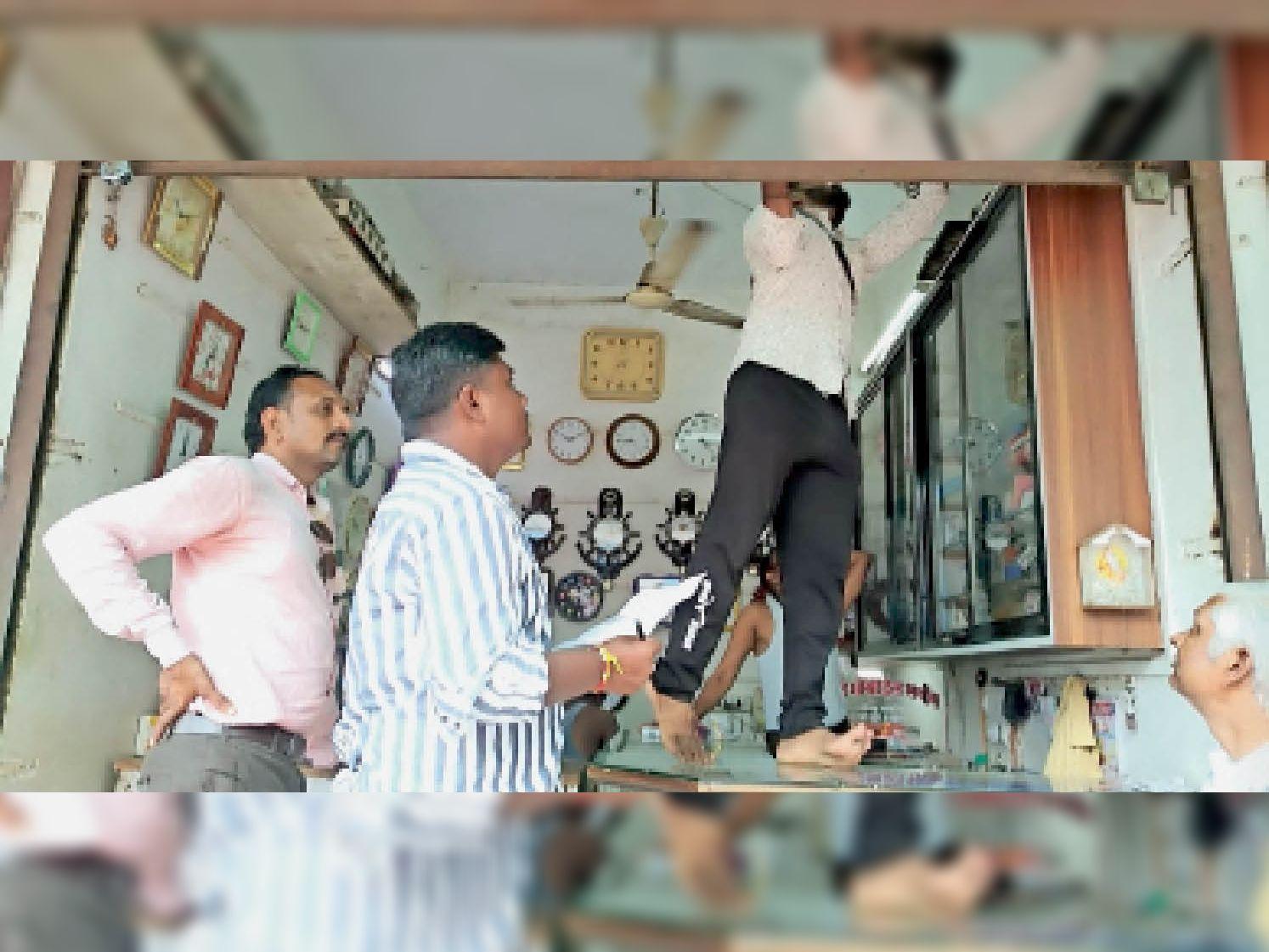 नगर में दुकानों पर मीटरों की जांच करते बिजली कंपनी के कर्मचारी। - Dainik Bhaskar
