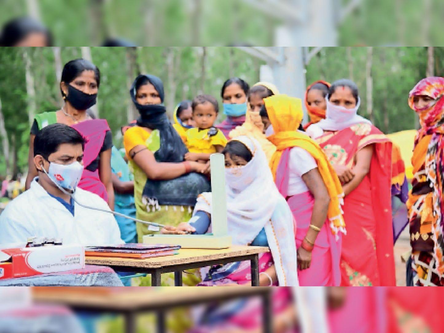 साप्ताहिक हाट में ग्रामीणांे का इलाज करते डॉक्टर। - Dainik Bhaskar