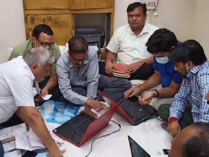छापामार कार्रवाई के दौरान दस्तावेज देखती टीम। - Dainik Bhaskar