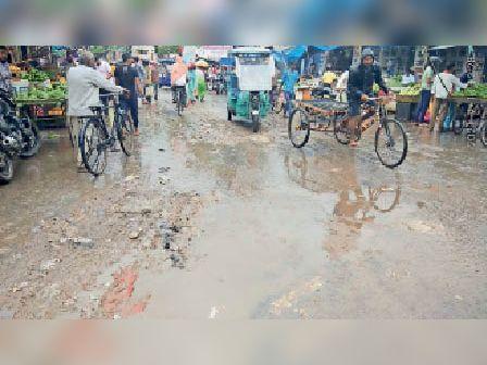 मंगलवार को हुई बारिश के बीच कीचड़ से आते-जाते लोग। - Dainik Bhaskar