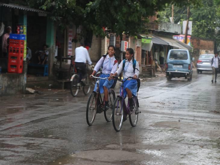 वाराणसी स्थित लंका क्षेत्र में बारिश में भीग कर स्कूल से आती बालिकाएं।