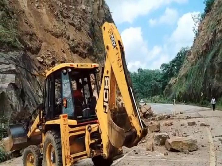 JCB की मदद से सड़क पर गिरे चट्टान के टुकड़ों को हटाया जा रहा है।