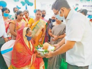 पोषण कार्यक्रम के तहतमहिला को पोषण सामग्री देते डीएम - Dainik Bhaskar