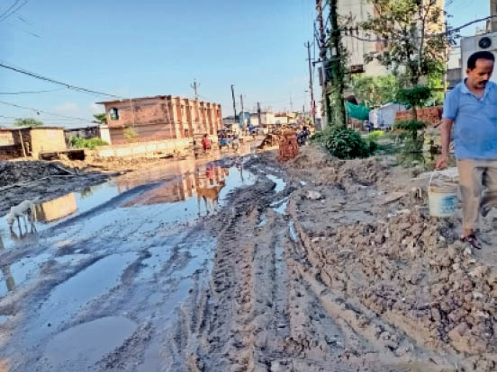 मुख्य सड़क पर फैली कीचड़ व मिट्टी का ढेर। - Dainik Bhaskar