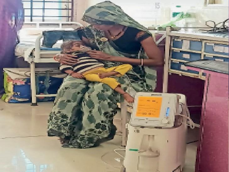 ये कैसी बेबसी... जिला अस्पताल में मरीजों की कतार लगी है। अस्पताल में पलंग तक नहीं मिल रहे। पलंग की जगह स्टूल पर बैठकर मां को बच्चे काे गोदी में लेकर इलाज करवाना पड़ रहा है। - Dainik Bhaskar