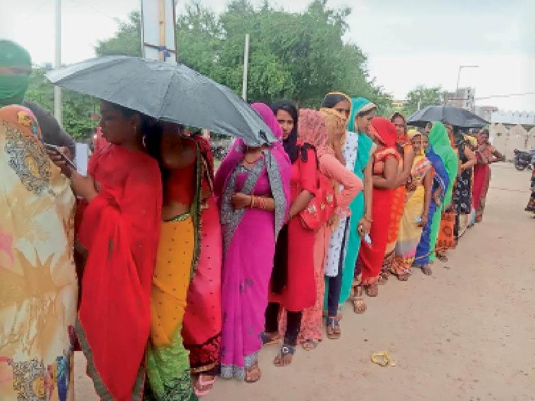 बारिश में भी वैक्सीन के लिए सदर अस्पताल में लाइन में खड़ी महिलाएं। - Dainik Bhaskar