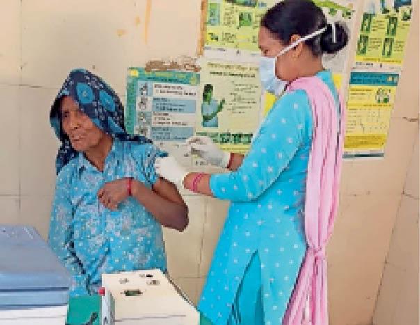 कैथल| बुजुर्ग महिला को वैक्सीन लगाती स्वास्थ्य कर्मी। - Dainik Bhaskar