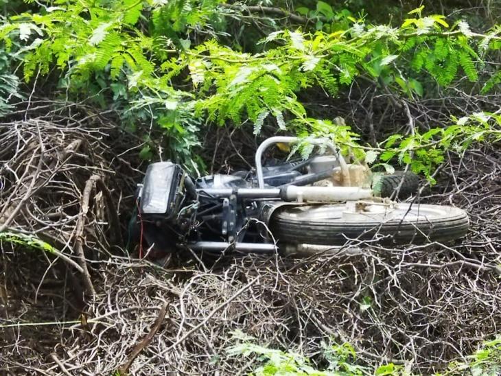 झाड़ियों में पड़ी क्षतिग्रस्त बाइक।