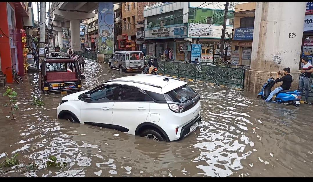 बरसात के पानी में बंद हुई कार।