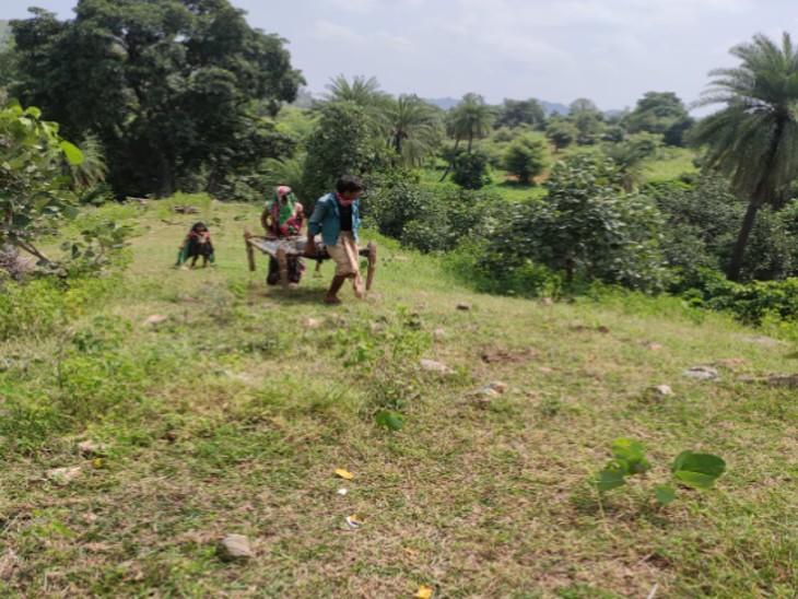बुजुर्ग महिला को चारपाई पर लिटाकर पहाड़ी पर ले जाते हुए परिजन। रास्ता मुश्किल होने की वजह से ये लोग थोड़ी-थोड़ी दूरी पर आराम के लिए भी रुकते रहे।