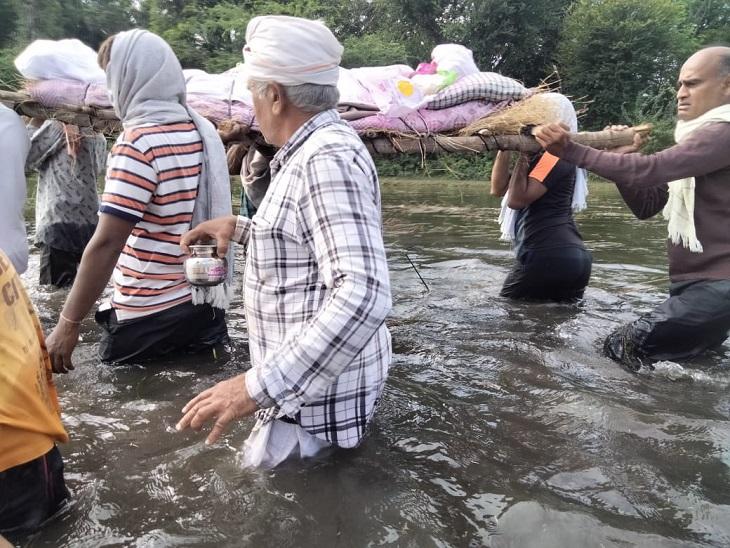 कमर तक पानी में डूबकर शव को ले जाते लोग।
