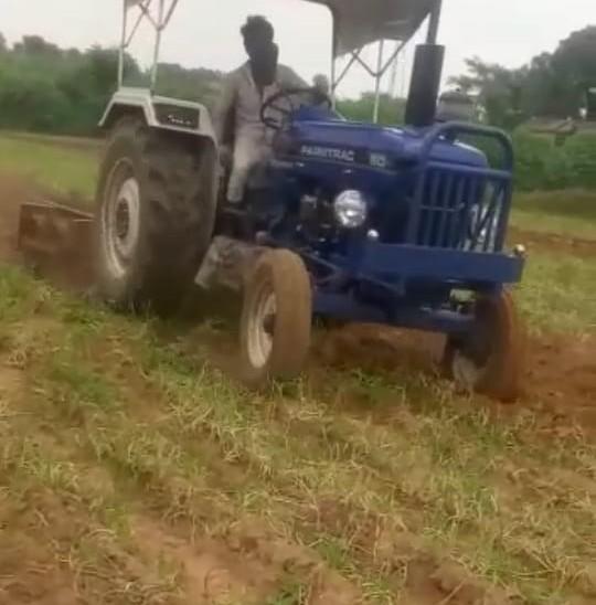 अलवर शहर के पास ढहरा में प्याज की फसल पर ट्रैक्टर चलाता किसान।