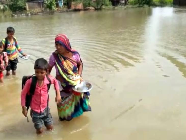 पानी के बीच बच्चों को स्कूल छोड़ने जाते उनके परिजन।
