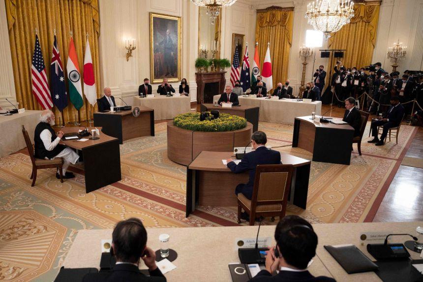 यह क्वॉड देशों की ऑफिशियल मीटिंग की फोटो है। बाएं तरफ PM मोदी बैठे हैं, उनके ठीक बगल में US प्रेसिडेंट जो बाइडेन, दाएं तरफ ऑस्ट्रेलियाई PM स्कॉट मॉरिसन हैं, और उनके सामने जापानी PM योशिहिदे सुगा। बाइडेन के पीछे चारों देशों के झंडे भी लगे हुए हैं।