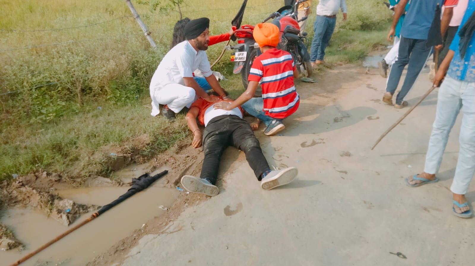 गाड़ी से पलटने से घायल हुए अपने साथी को संभालते हुए किसान।