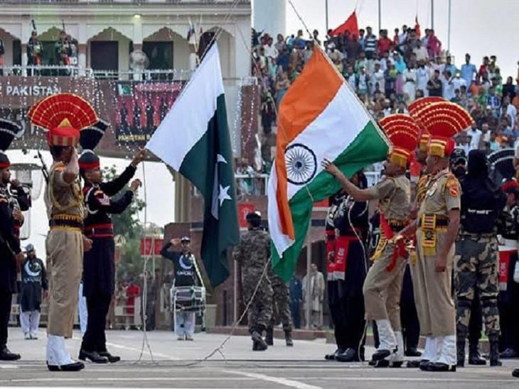 परेड के दौरान झंडा उतारने की रस्म अदा करते बीएसएफ व पाक रेंजर्स के जवान।