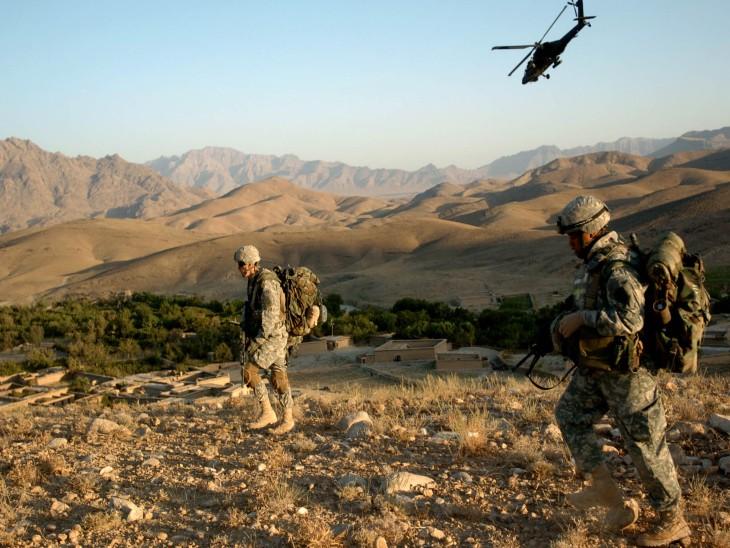 अफगानिस्तान युद्ध के दौरान गश्त करते अमेरिकी सैनिक। सैनिकों के बैकअप के लिए अपाचे हेलिकॉप्टर भी तैनात था।
