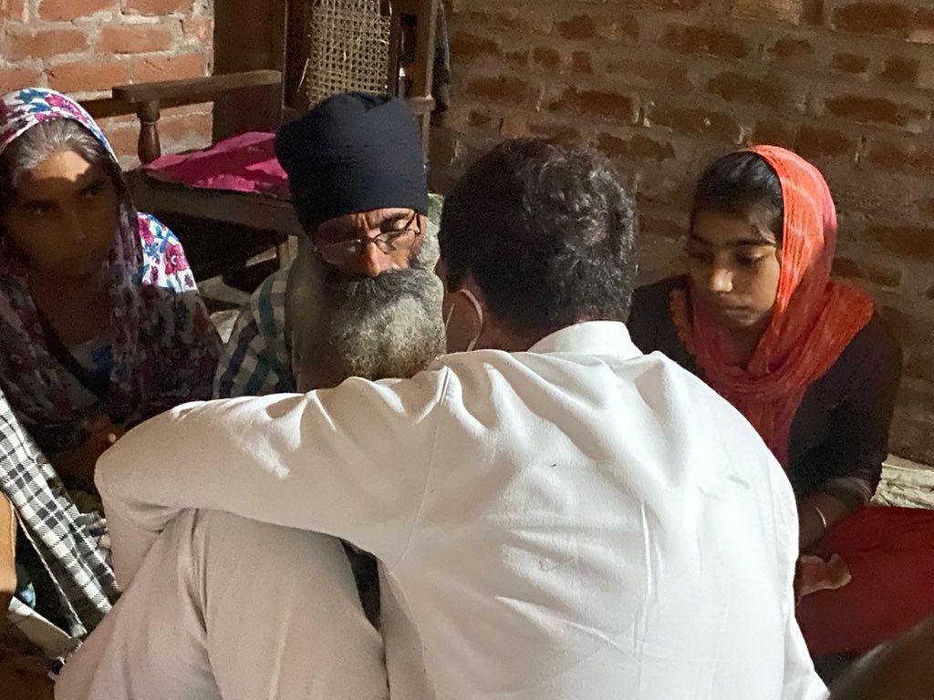 पलिया में लवप्रीत के माता-पिता से बातचीत करते राहुल गांधी।