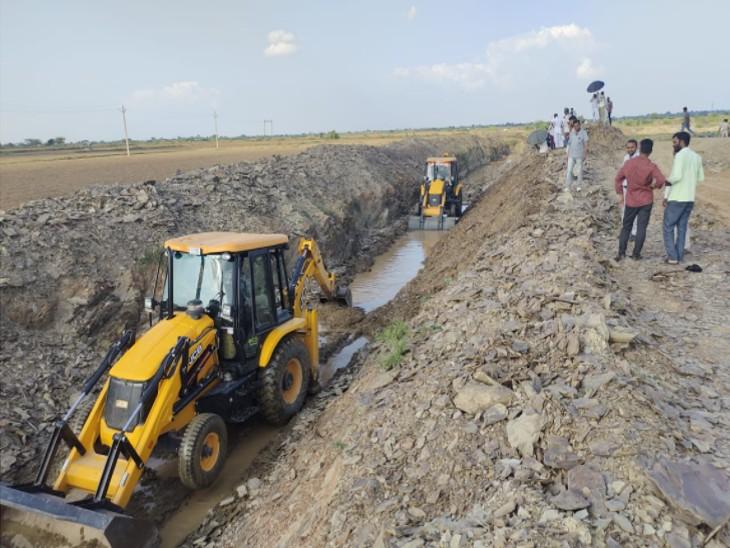 भोमपुरा बांध से जेसीबी की मदद से पानी की निकासी कराते अधिकारी। - Dainik Bhaskar