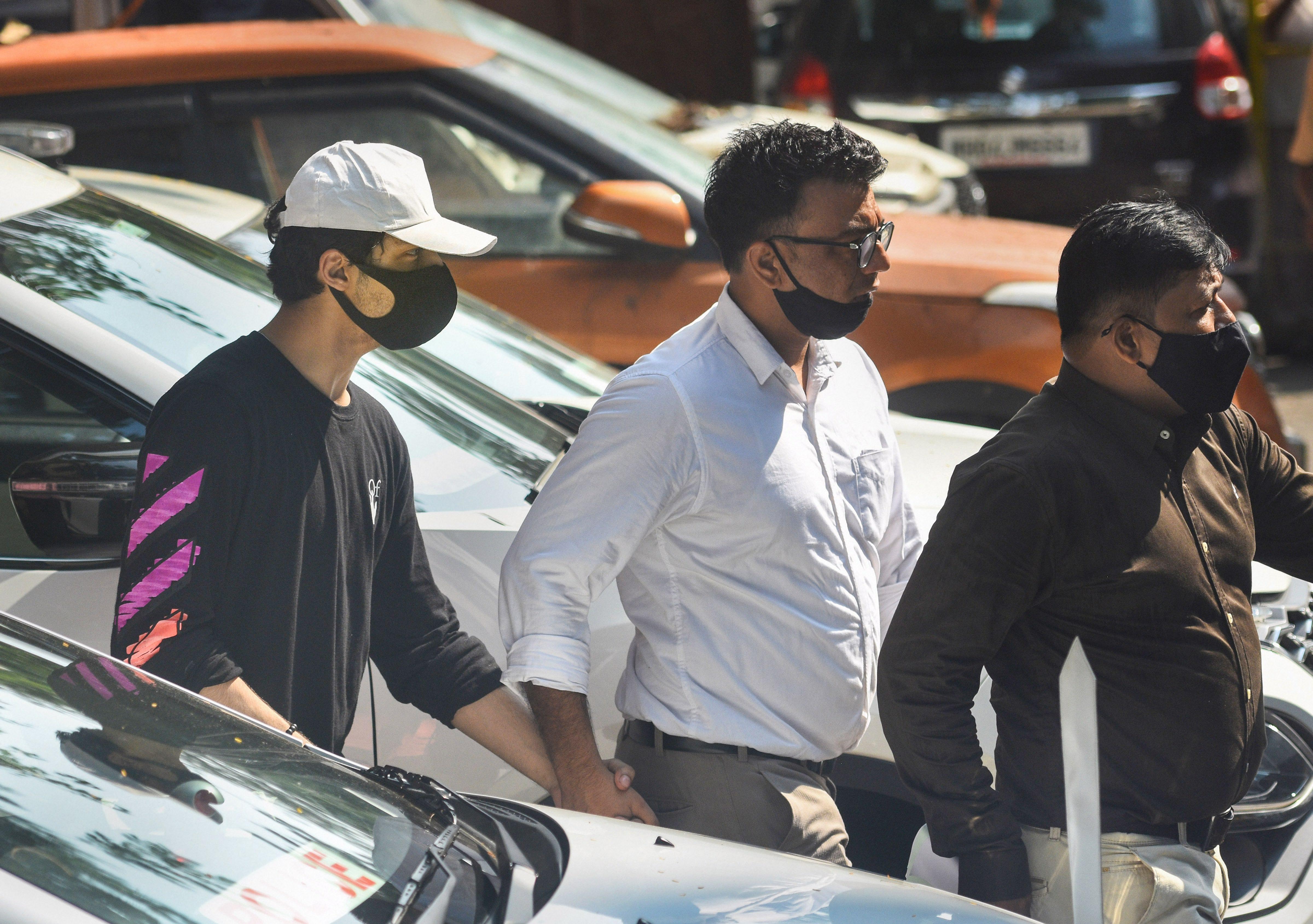 आर्यन की यह तस्वीर उन्हें NCB ऑफिस से अदालत ले जाने के दौरान की है। इसमें आर्यन ने ब्लैक रंग की स्वेटशर्ट और सफेद रंग की टोपी पहनी थी।