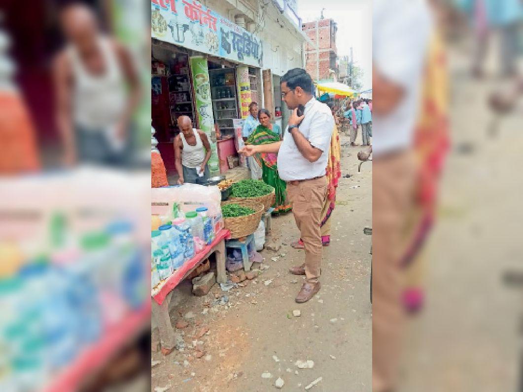 मुख्य बाजार सिमरीबख्तियारपुर में फुटपाथी दुकानदार को समझाते ईओ। - Dainik Bhaskar