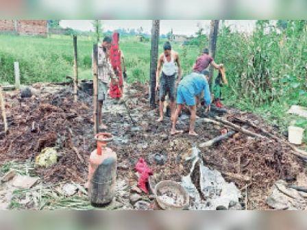 पचफेड़वा में जले घर के राख की ढेर में सामान खोजते पीड़ित। - Dainik Bhaskar