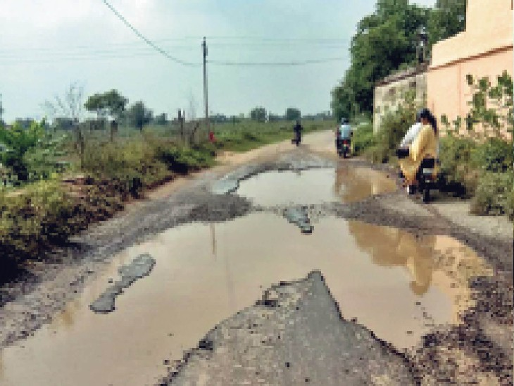 पिलानी. बेरी गांव में शहीद पीरू सिंह स्मारक तक की टूटी सड़क पर गड्ढों में भरे पानी के कारण बचकर किनारे से निकलते बाइक सवार। - Dainik Bhaskar
