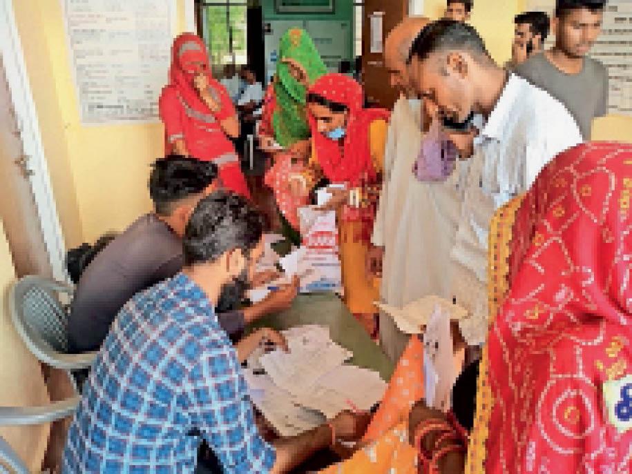 गांव में लगाए गए सुकन्या योजना मेले में रजिस्ट्रेशन करवाते ग्रामीण। - Dainik Bhaskar