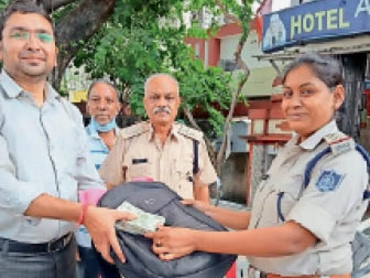 सागर  पुलिस की मौजूदगी में अनुराग दुबे को बैग लौटाते हुए। - Dainik Bhaskar