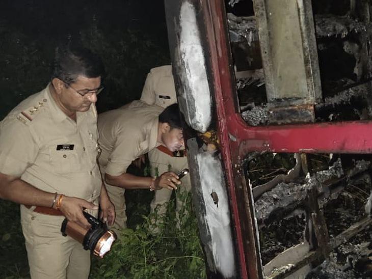 आग पर काबू पाने के बाद बस के अंदर झांककर देखते पुलिस कर्मी।