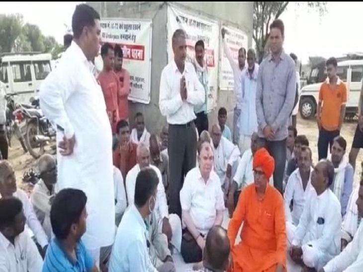 धरने पर बैठे हुए ग्रामीणों से बात करते सांसद। - Dainik Bhaskar