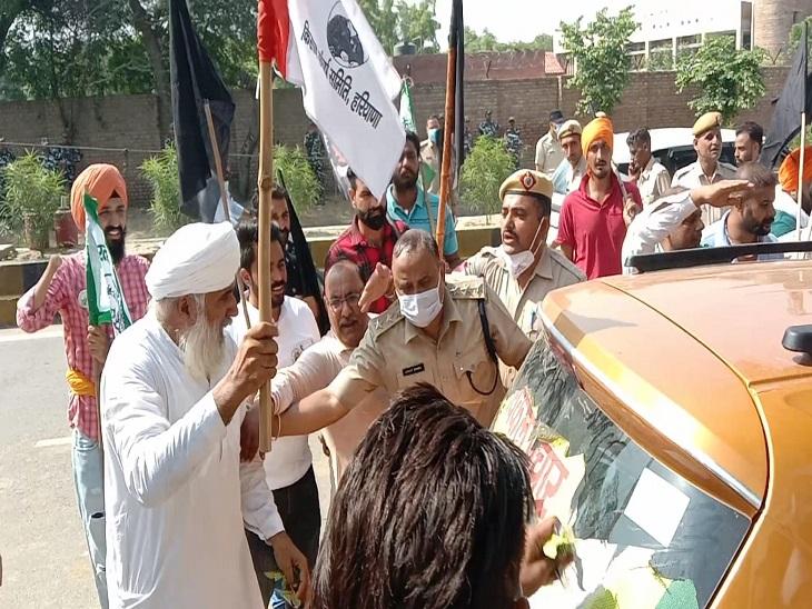 विकल प्रचार की गाड़ी पर लगे पोस्टर फाड़ रहे किसानों को हटाते पुलिसकर्मी।