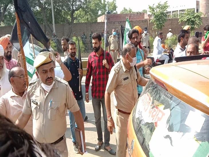 विकल पचार की गाड़ी पर लगे पोस्टर फाड़ रहे किसानों को हटाते पुलिसकर्मी।