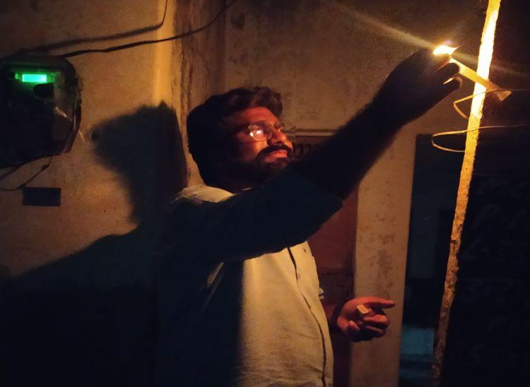 इन्द्रा कॉलोनी में पूर्व पार्षद रोडलाइट पोल पर मोमबत्ती जलाते हुए।