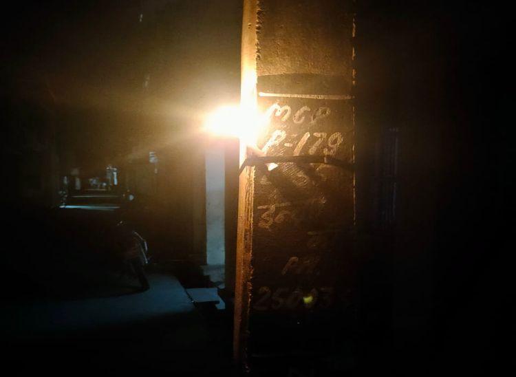 पाली के इन्द्रा कॉलोनी में लाइट के पोल पर जल रही मोमबत्ती।