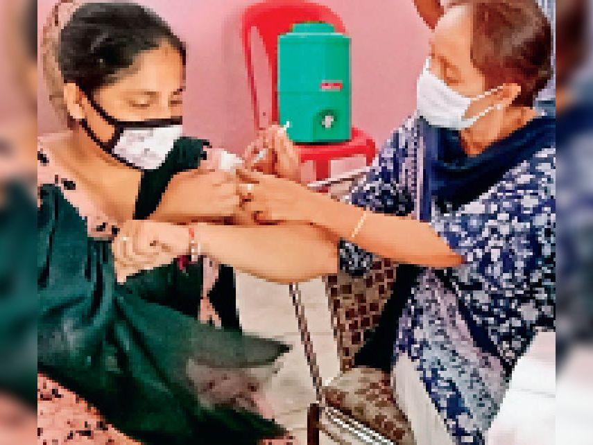वैक्सीनेशन कैंप में वैक्सीन लगवाते लाभार्थी। - Dainik Bhaskar