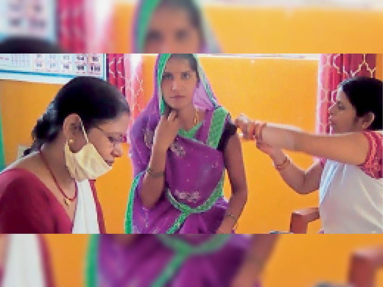 वैक्सीन लगवाती महिला। - Dainik Bhaskar