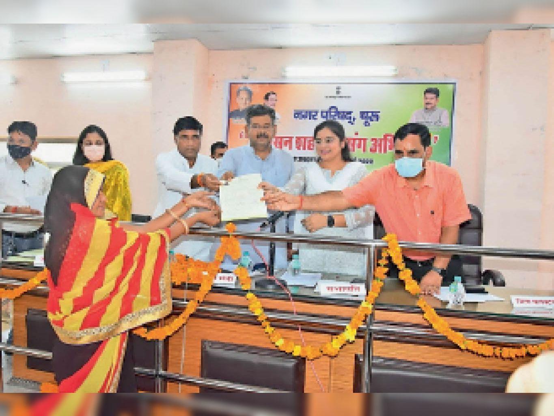 नगरपरिषद में आयोजित शिविर के दौरान लाभार्थी को पट्टा प्रदान करते प्रभारी मंत्री भाटी व अन्य। - Dainik Bhaskar