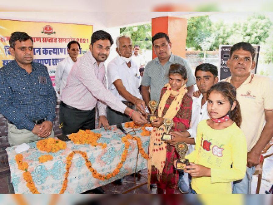 कार्यक्रम के दौरान दिव्यांगों को सम्मानित करते अतिथि। - Dainik Bhaskar