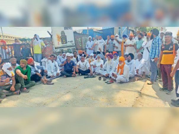 मंडी के गेट पर धरने पर बैठकर विरोध जताते किसान। - Dainik Bhaskar