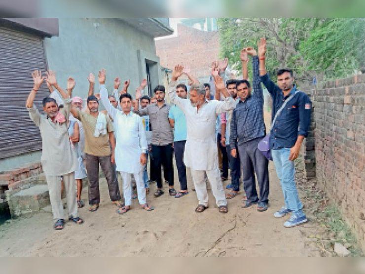सड़क निर्माण की मांग को लेकर प्रदर्शन करते हुए जलघर के नजदीक रहने वाले लोग। - Dainik Bhaskar