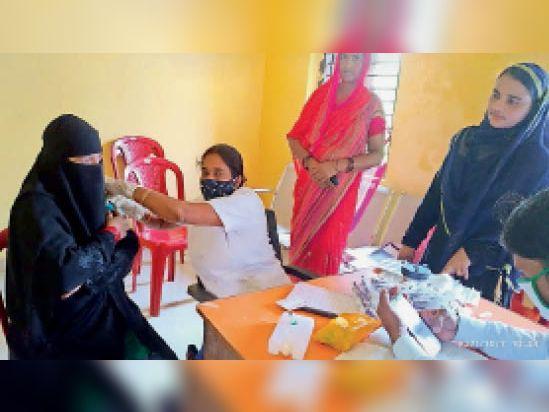 महिला को कोरोनारोधी वैक्सीन देती स्वास्थ्यकर्मी। - Dainik Bhaskar