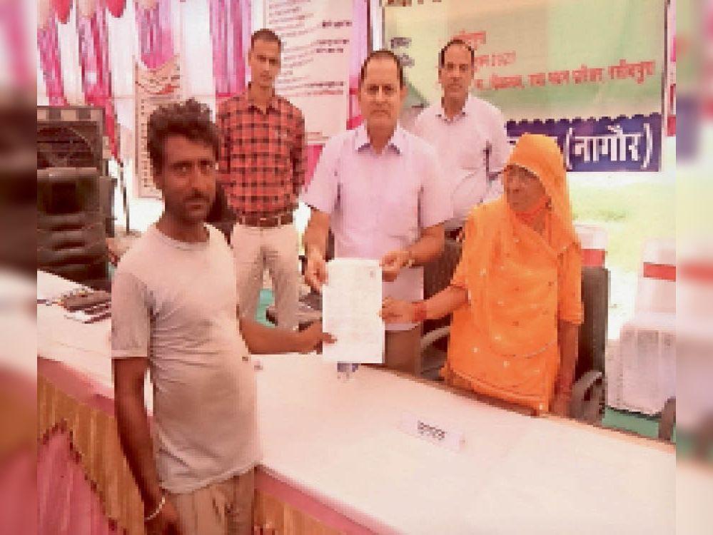 रसीदपुरा में सरपंच व एडीएम पट्टा वितरण करते हुए। - Dainik Bhaskar