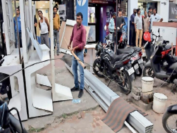 टूटे बिजली तार को हटाता दुकानदार। - Dainik Bhaskar