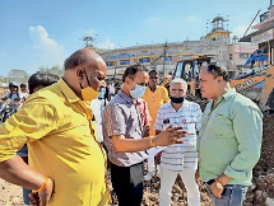 नयापुरा चौराहा का काम धीमी गति से चलने पर यूआईटी के एक्सईएन के समक्ष जताते नयापुरा व्यापार संघ के उपाध्यक्ष महेश आहूजा व अन्य व्यापारी। - Dainik Bhaskar