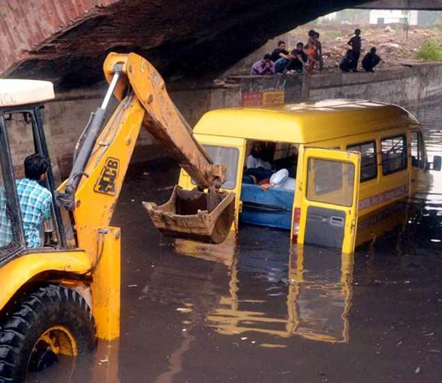 ब्रिजखाली अडकलेल्या स्कूलबसला बाहेर काढताना जेसीबी - Divya Marathi