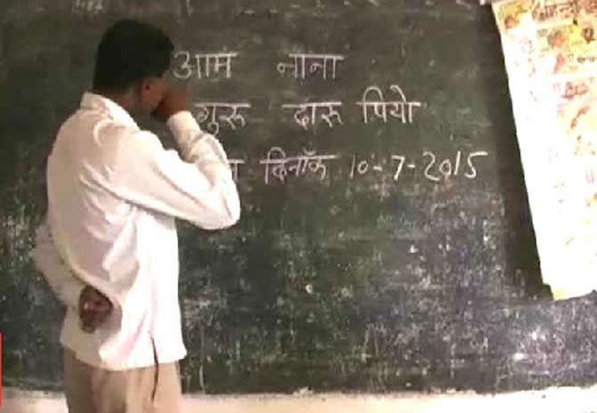 फळ्यावर दारू प्या असे लिहून शिकवताना शिक्षक. - Divya Marathi